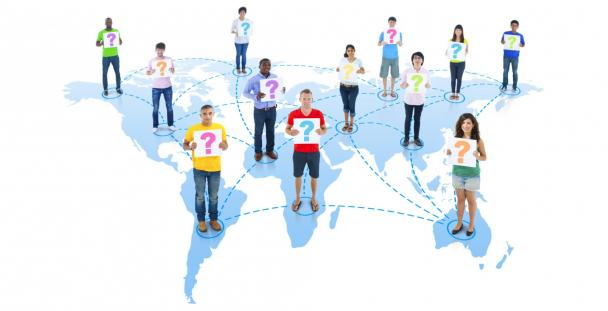 Image of people holding question marks standing on a map of the world
