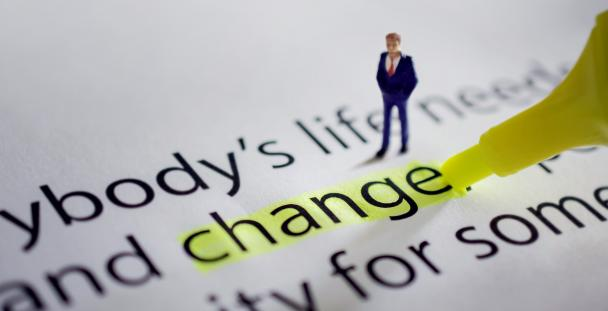 Image of a small model of a man next to the word change