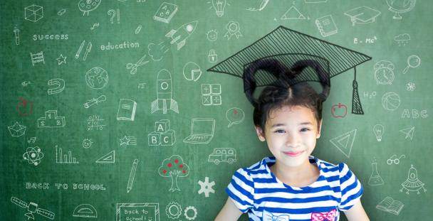 Image of a child in front of a chalk board covered in educational symbols