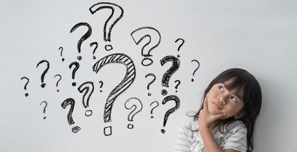 Child looking inquisitive next to question marks