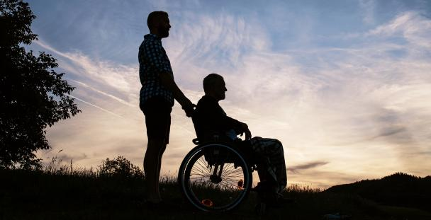 Image of the silhouette of a man pushing another man in a wheelchair