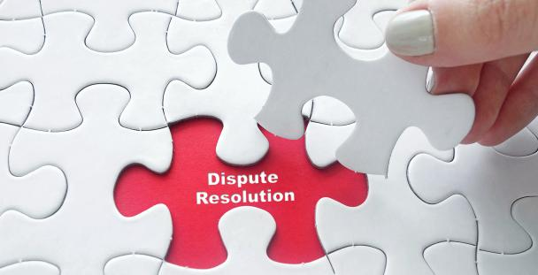 Image of jigsaw pieces with one displaying the words dispute resolution