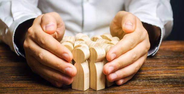 Image of a pair of hands surrounding wooden models of people illustrating job retention