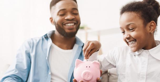 Image of a father and daughter with a piggy bank