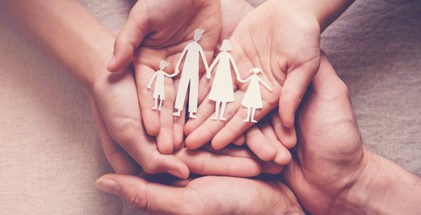 Image of hands holding a set of wooden family figures