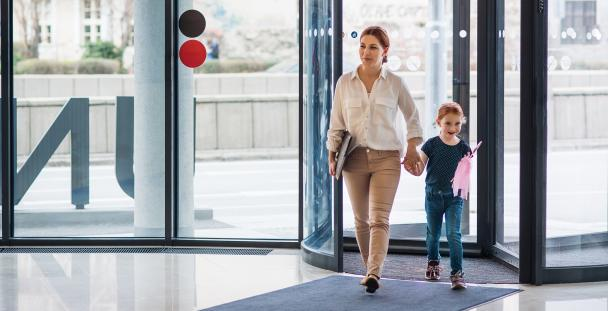 Image of a woman and child walking into an office