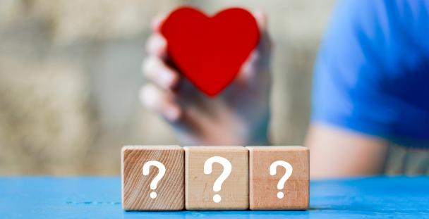 Image of a person holding a paper heart with question marks in front