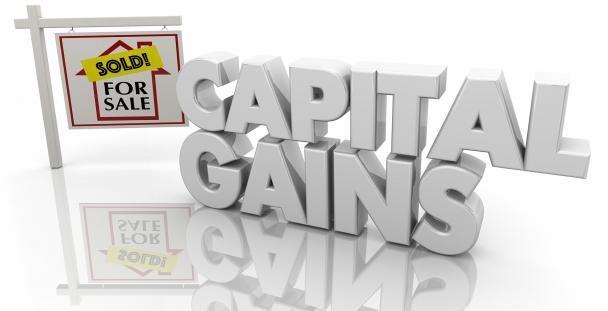 Image of the words capital gains and a for sale sign
