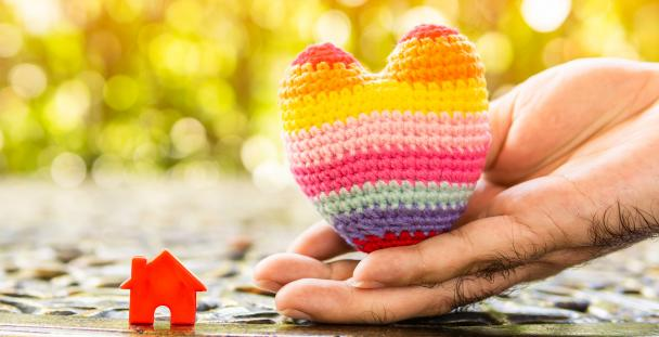 Image of a hand holding a knitted heart next to a small model house