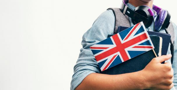 Image of student holding books and a Union Jack flag