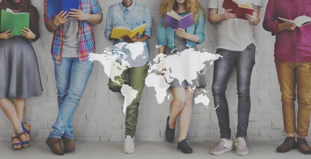 Image of international students with a map of the world in front