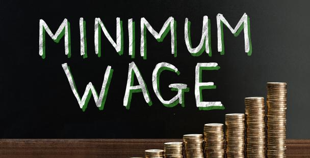 Image of the words minimum wage and stacks of coins