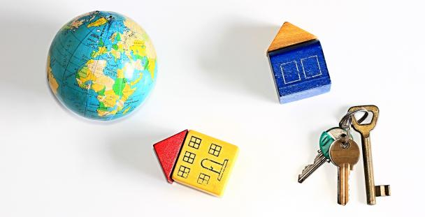 Image of a globe, two houses and a set of keys