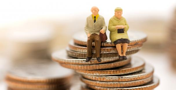 Image of models of pensioners sitting on a pile of coins