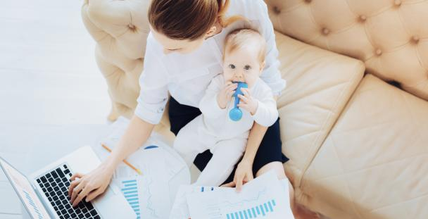 Image of a woman working with baby on her lap