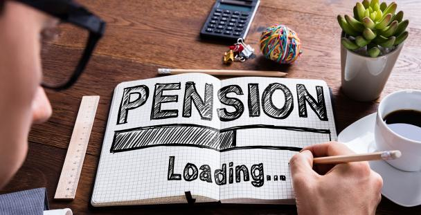 Image of a man writing pension... loading in a notebook