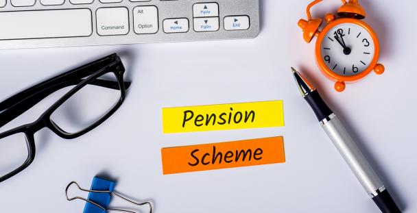 Image of office equipment with the words pension scheme written on pieces of paper