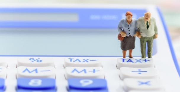 Model of pensioner couple standing on calculator with tax button