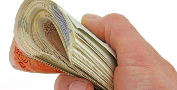 Image of a person holding UK bank notes