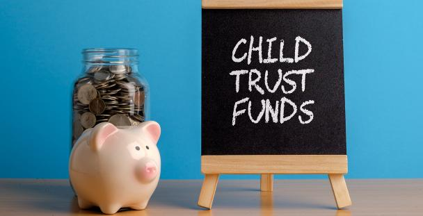 Image of a piggy bank and a board with the words child trust funds written on it