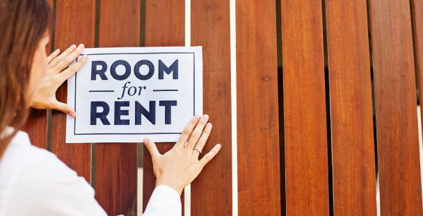 Image of a woman attaching a room to rent sign on a wall