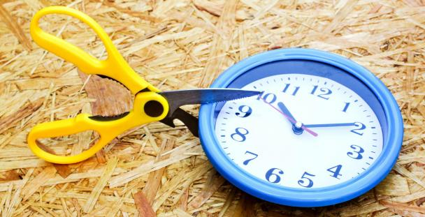 scissors cutting into a clock to signal cut in working hours
