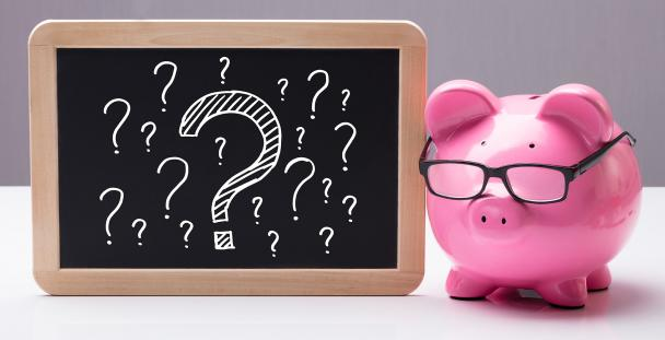 Image of a piggy bank next to a blackboard displaying question marks