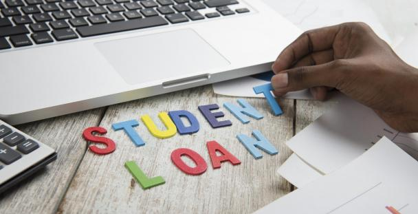 Image displaying letters spelling student loan in front of a laptop