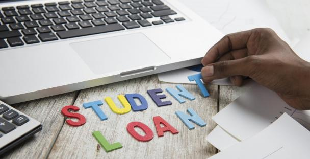 Student loan spelt out in front of a laptop
