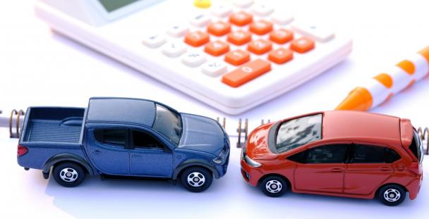 Miniature van and car next to a calculator illustrating vehicles and business travel