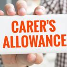 Image of a person hold a sign saying carer's allowance
