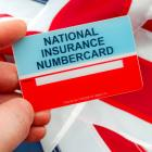 Hand holding a National Insurance card in front of a Union Jack flag